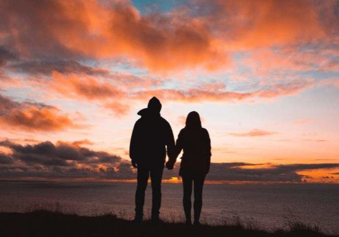 couple standing in front of an amber sunset