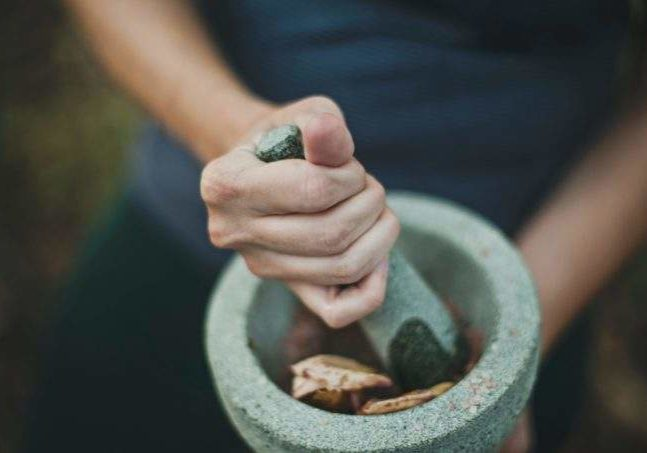 someone using a mortar and pestle