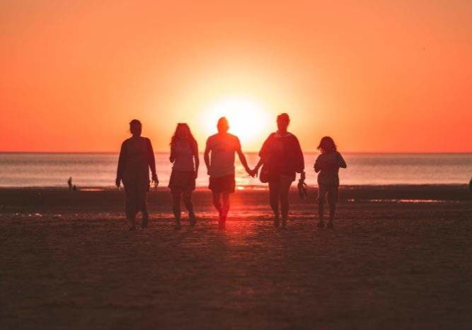 Silhouetted family of five walking at a beach at sunset.